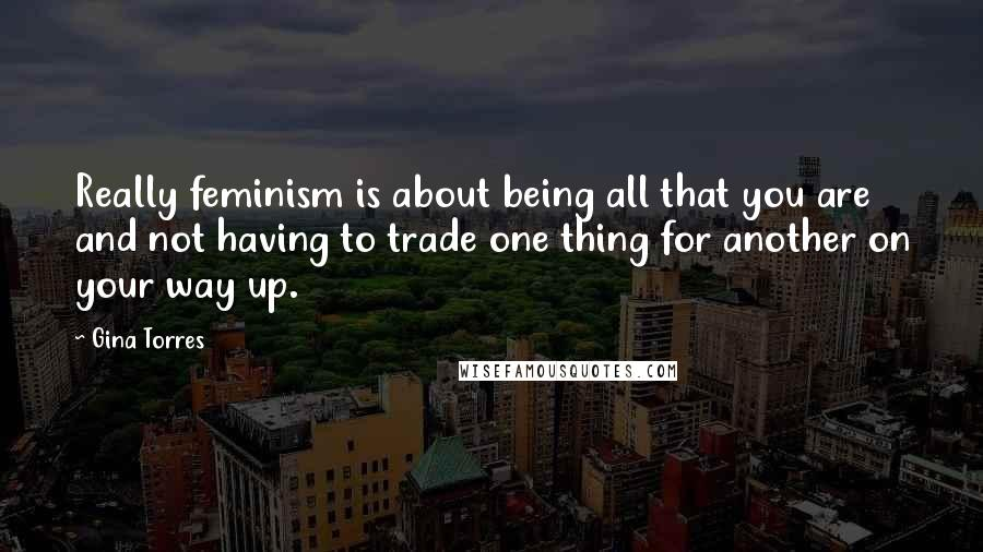 Gina Torres quotes: Really feminism is about being all that you are and not having to trade one thing for another on your way up.