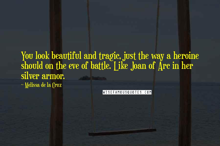Melissa De La Cruz quotes: You look beautiful and tragic, just the way a heroine should on the eve of battle. Like Joan of Arc in her silver armor.