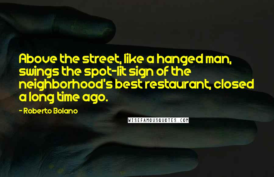 Roberto Bolano quotes: Above the street, like a hanged man, swings the spot-lit sign of the neighborhood's best restaurant, closed a long time ago.