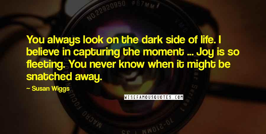 Susan Wiggs quotes: You always look on the dark side of life. I believe in capturing the moment ... Joy is so fleeting. You never know when it might be snatched away.