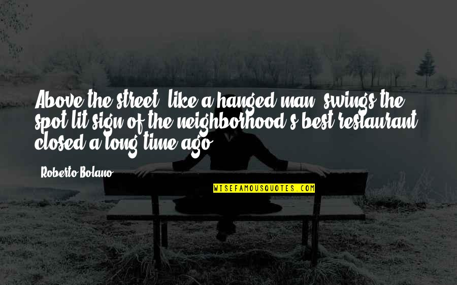 Time Of Quotes By Roberto Bolano: Above the street, like a hanged man, swings