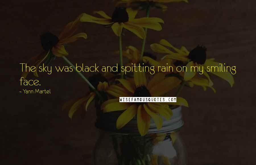 Yann Martel quotes: The sky was black and spitting rain on my smiling face.